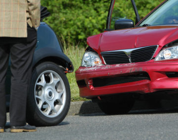 person standing at car after care accident